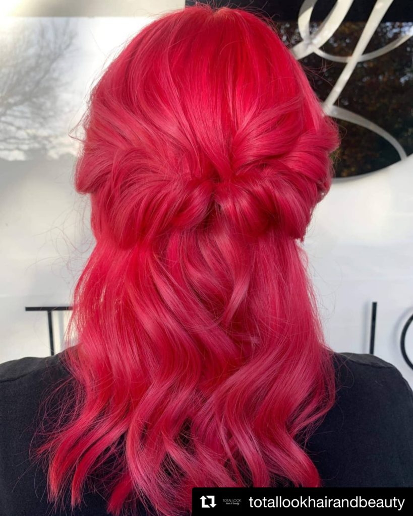 Image of the back of Karen's head. Her hair is medium length, wavy and is coloured a vibrant pink.