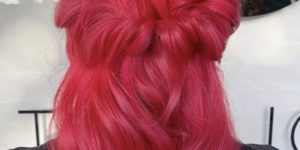 Image of the back of Karen's head. Her hair is medium length, wavy and coloured a vibrant pink.